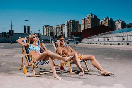 young attractive couple relaxing on sun loungers relaxing on parking