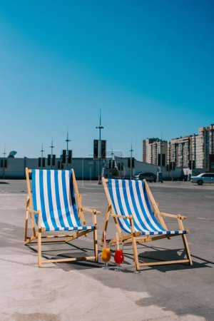 sun loungers with cocktail on parking on sunny summer day