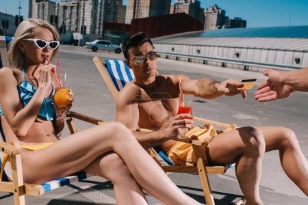 young couple with cocktails sitting on sun loungers and paying with credit card on parking