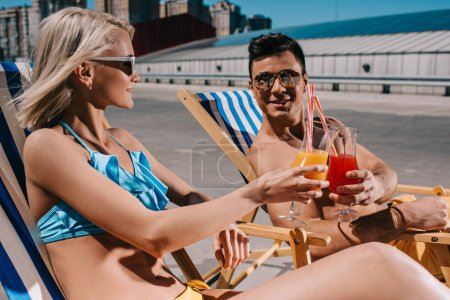 young couple clinking glasses of cocktails while sitting on sun loungers on parking