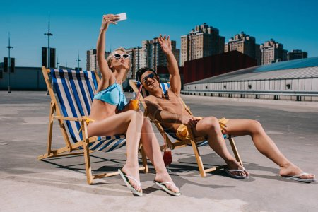 young couple relaxing on sun loungers with cocktails and taking selfie on parking