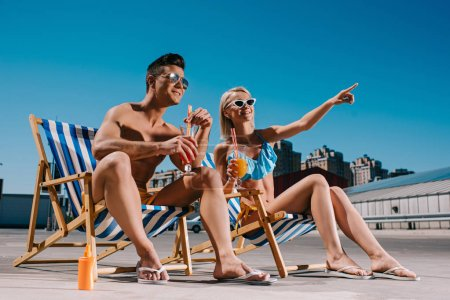 young couple with cocktails sitting on sun loungers on parking