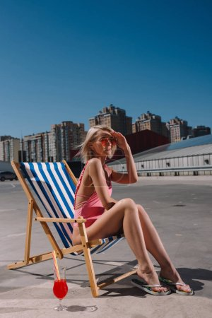 stylish young woman relaxing in sun lounger on parking