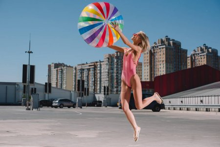 beautiful young woman in swimsuit jumping with colorful beach ball on parking