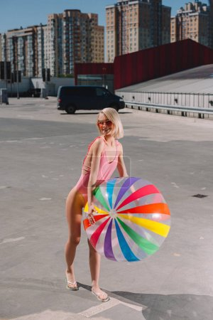 attractive young woman in swimsuit with colorful beach ball on parking