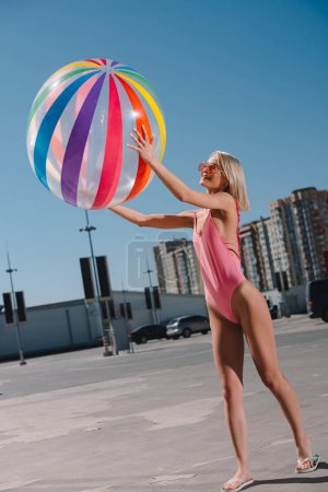 happy young woman in swimsuit with colorful beach ball on parking