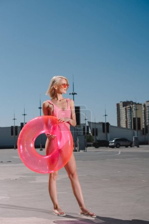 young woman in stylish pink swimsuit with inflatable ring on parking