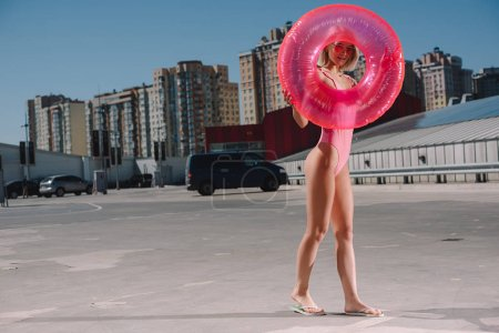 attractive young woman in swimsuit with inflatable ring on parking