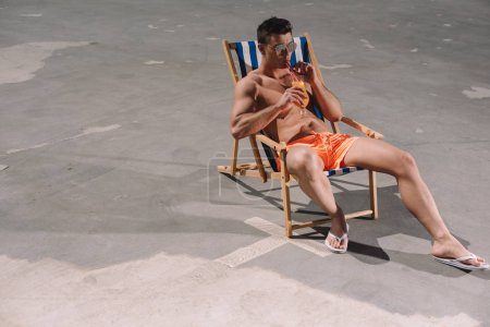 high angle view of young shirtless man drinking cocktail while relaxing in sun lounger on asphalt