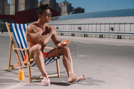 handsome young shirtless man sitting on sun lounger and applying sunscreen lotion on parking