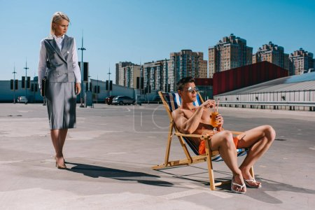 handsome young man relaxing on sun lounger while his lady boss in suit standing next to him on parking