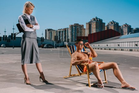 handsome young man relaxing on sun lounger while his lady boss in suit standing next to him with crossed arms on parking