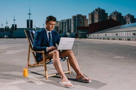 Photo pour Beau jeune homme d'affaires en short et veste de travail avec ordinateur portable tout en étant assis sur une chaise longue sur le parking - image libre de droit
