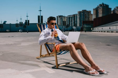 handsome young businessman in shorts working with laptop while sitting on sun lounger on parking and drinking cocktail
