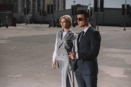 couple de jeunes entrepreneurs à la mode marchant sur un parking