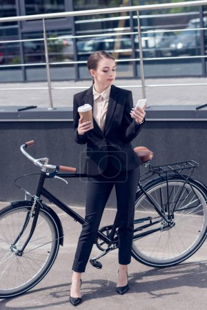 young businesswoman with coffee to go and smartphone standing near retro bicycle on street
