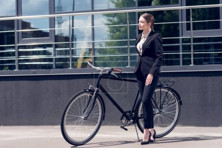 young businesswoman in suit and high heels standing near retro bicycle on street