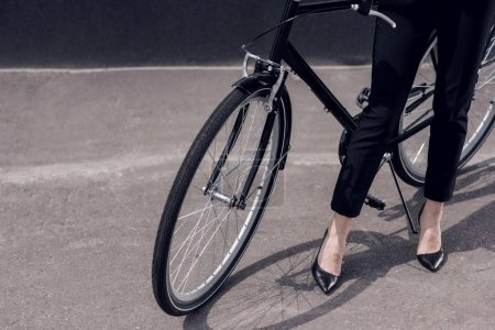 cropped shot of businesswoman in suit and high heels standing near retro bicycle on street