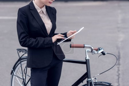 partial view of businesswoman using digital tablet while standing near retro bicycle on street
