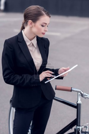 young businesswoman using digital tablet while standing near retro bicycle on street