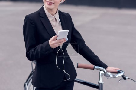 cropped shot of businesswoman in earphones with smartphone standing near retro bicycle on street