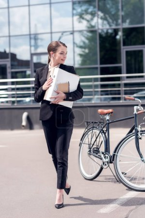 young businesswoman in earphones with documents walking on street with bicycle parked behind