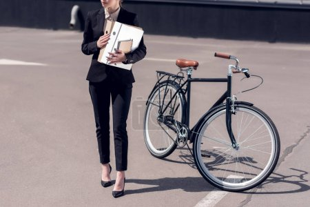 partial view of businesswoman with documents walking on street with bicycle parked behind