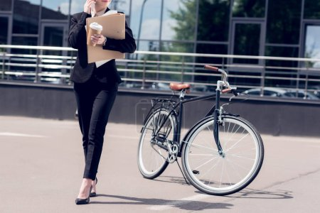 cropped shot of businesswoman with documents and coffee to go talking on smartphone while walking on street with bicycle parked behind