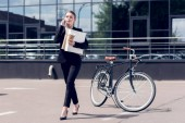 businesswoman with documents and coffee to go talking on smartphone while walking on street with bicycle parked behind