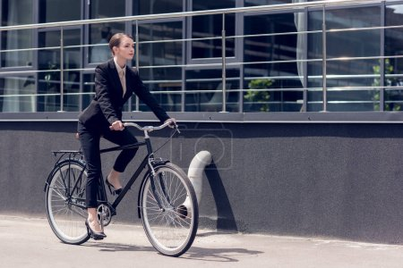 side view of young stylish businesswoman in suit riding retro bicycle