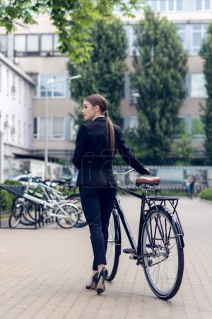 back view of young businesswoman standing near retro bicycle on street