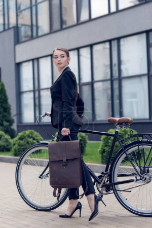 side view of young businesswoman with briefcase and retro bicycle on street