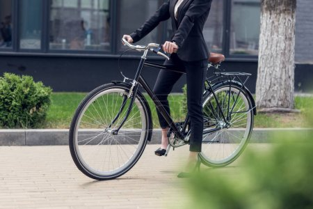 cropped shot of businesswoman in suit with retro bicycle on street