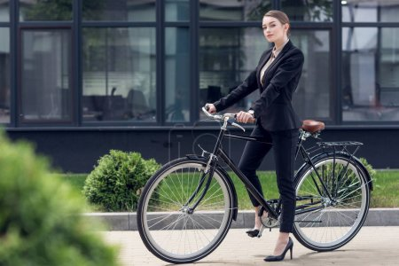 young businesswoman in black suit with retro bicycle on street