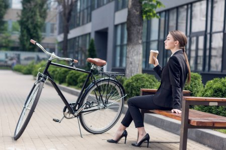 side view of young businesswoman with coffee to go resting on bench with retro bicycle parked near by