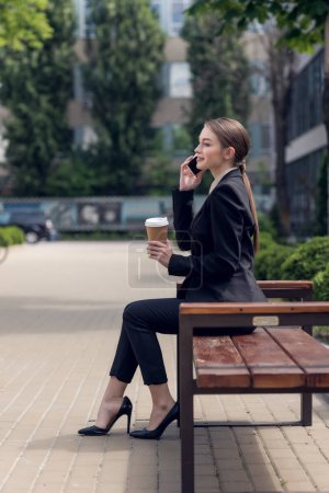 side view of young businesswoman with coffee to go talking on smartphone while resting on bench