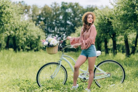 young beautiful woman standing near retro bicycle with wicker basket full of flowers in forest
