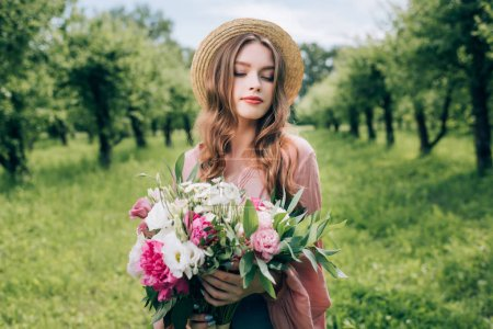 Photo for Portrait of young woman in hat with bouquet of flowers in hands in park - Royalty Free Image
