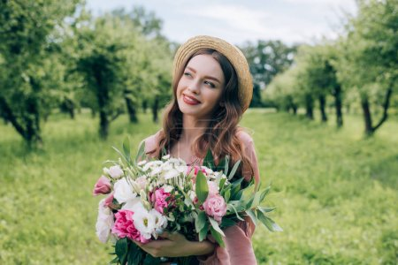 portrait of beautiful smiling woman in hat with bouquet of flowers looking away in park