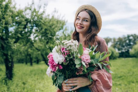 portrait of pretty young woman in hat with bouquet of flowers in park