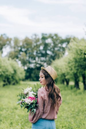 back view of young woman in hat with bouquet of flowers in hands standing in park