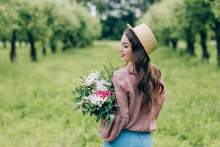 back view of smiling woman in hat with bouquet of flowers in hands standing in park