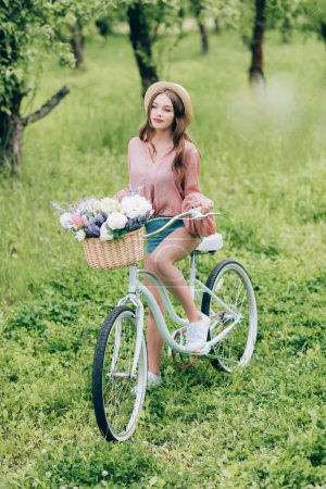 young woman on retro bicycle with wicker basket full of flowers in forest