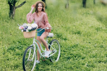 pretty smiling woman on retro bicycle with wicker basket full of flowers in forest