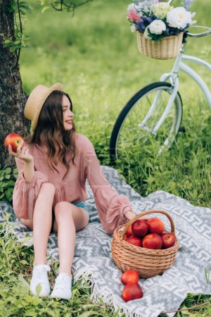 pretty smiling woman in hat resting on blanket with wicker basket with apples and bicycle parked near by in park