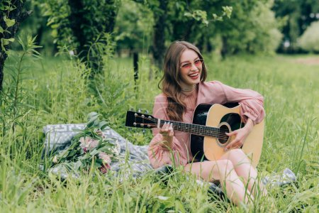 happy woman in sunglasses with acoustic guitar resting on blanket with bouquet of flowers in park
