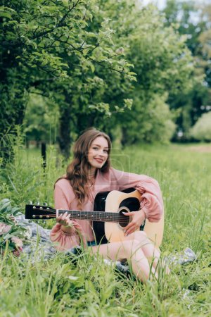 young smiling woman with acoustic guitar resting on blanket with bouquet of flowers in park