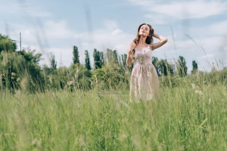 young pretty woman in stylish dress standing in meadow alone