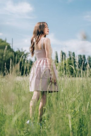 back view of young pensive woman in stylish dress standing in meadow alone