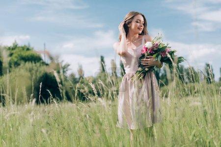 Foto de Retrato de hermosa mujer joven con ramo de flores mientras está parado en el campo solo - Imagen libre de derechos